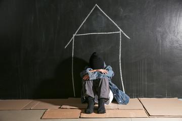 Homeless little girl sitting on floor near dark wall