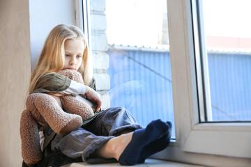 Homeless little girl with teddy bear sitting on window sill
