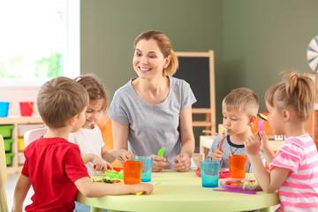 Nursery teacher with cute little children during lunch in kindergarten