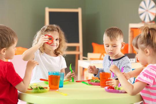 Cute little children eating tasty lunch in kindergarten