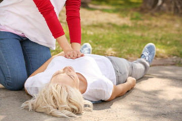 Female passer-by doing CPR on unconscious mature woman outdoors