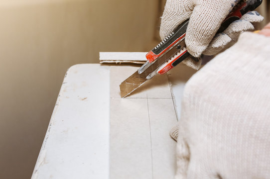 Man is cutting gypsum board with utility knife. Maintenance repair works renovation in the flat . Restoration indoors. Drywall panel.