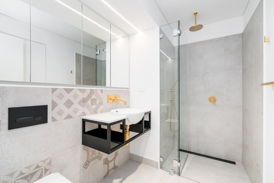 Modern industrial style bathroom interior with floor to ceiling tiling and black and gold fittings.