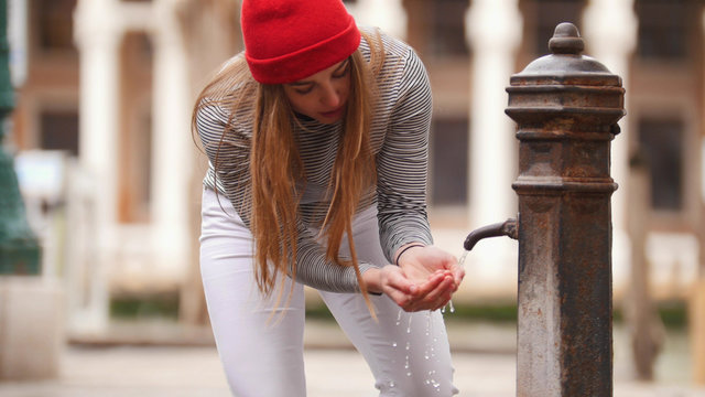 A young woman drinks water from a street fountain - filling her hands with water