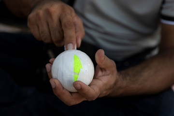 A Pakistani man living in Greece wraps a tennis ball in electrical tape before a tape-ball cricket game in a park in the Agioi Anargyroi suburb in Athens