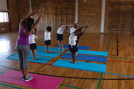 Female yoga teacher teaching yoga to school kids in school