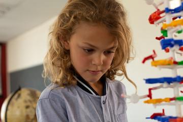 Schoolgirl learning on science model in classroom