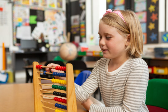 Schoolgirl learning mathematics with abacus in the classroom