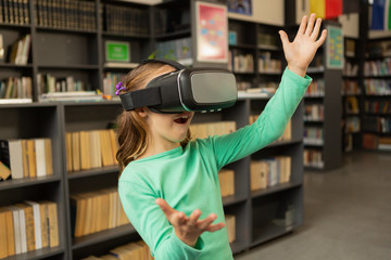 Schoolgirl using virtual reality headset in library