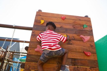 Schoolboy climbing a wall in the school playground