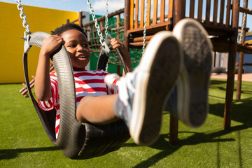Schoolboy playing on a swing at school playground