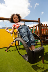 Schoolgirl playing on a swing at school playground