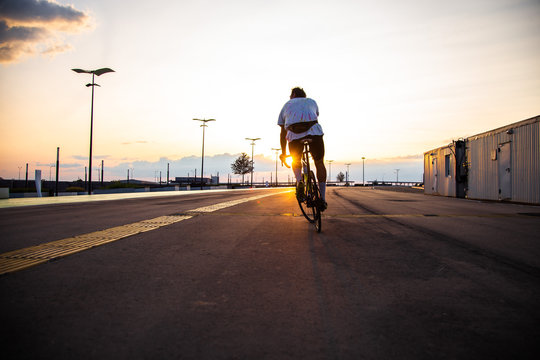a man ride a bicycle at sunset with sunbeam over Urban landscape, road