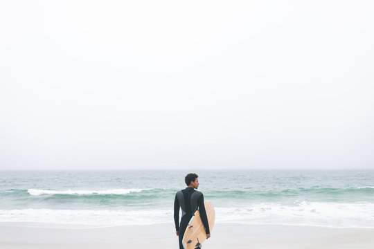 Male surfer holding surfboard on the beach