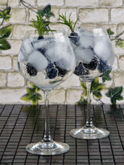Gin tonic decorated with a rosemary sprig, fresh berries and slices of lime