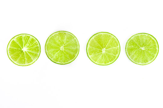 Vibrant lime slices, shot from above on a white background, a fresh fruity design element with a place for text