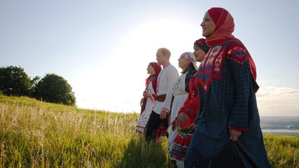 People in traditional russian clothes walking in a row on a meadow and singing a song