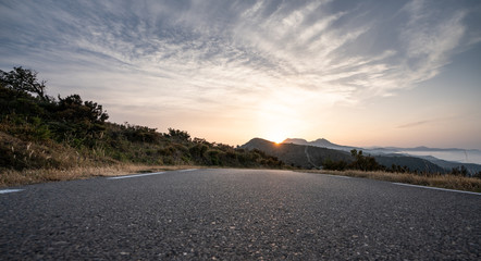 Wall Mural - Empty long road on a sunny summer day at bright sunset