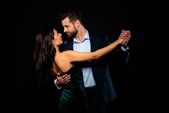 Close up back rear behind photo beautiful she her wife he him his husband mrs mr married spouse hold hands tango slow dance position gentle wear costume jacket green dress isolated black background