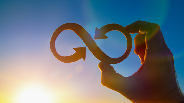 A symbol of infinity in the hand of a man against the sky and the glare of the sun, business concept idea.