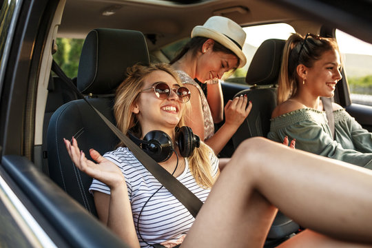 Three best female friends travel together.They drives a car and making fun.Sunset.