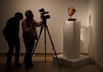 A camera crew films an Egyptian brown quartzite head of the God Amen which will be sold at auction at Christie's in London