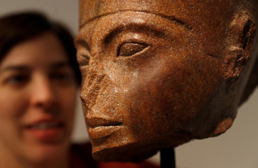 Laetitia Delaloye, head of antiquities of Christie's, poses for a photograph with an Egyptian brown quartzite head of the God Amen prior to its' sale at Christie's auction house in London