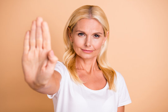 Photo of lady arm raised you will not pass through symbol wear white casual t-shirt isolated pastel beige background
