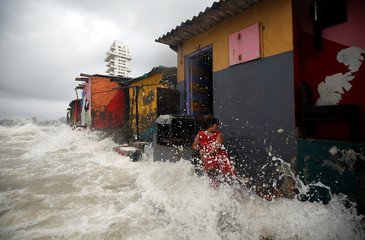 A woman gets drenched by a huge waves outside her house along a seafront during high tide in Mumbai