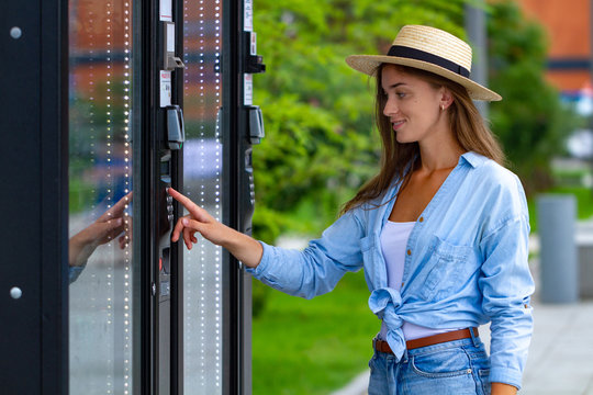 Young woman in hat using vending machine on the street during a walk around the city for buying soda and sweets