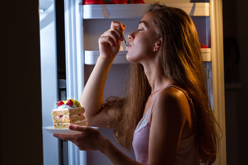 Hungry woman in pajamas enjoys sweet cake at night near refrigerator. Stop diet and gain extra pounds due to carbs food and unhealthy eating Fotoväggar