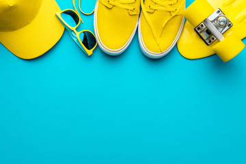 Top view of yellow modern teenage accessories. Flat lay image of yellow baseball cap, sunglasses, sneakers, plastic mini cruiser skateboard over blue turquoise background with copy space