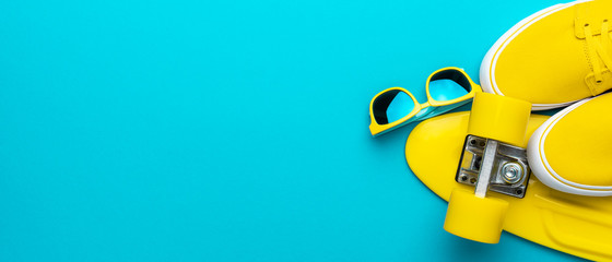 Top view panoramic image of yellow modern teenage accessories. Flat lay photo of yellow sunglasses, sneakers, plastic mini cruiser skateboard over blue turquoise background with copy space.