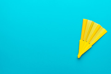 Top view of yellow hand fan over turquoise blue background with copy space. Minimalist flat lay photo of vivid plastic folding fan with right side composition.