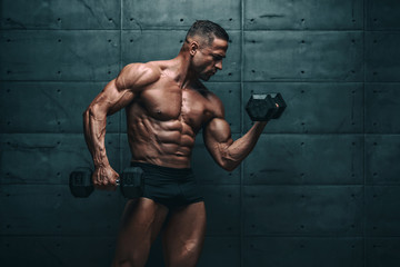 Muscular Men Exercise With Weights. He is performing biceps curls with dumbbels