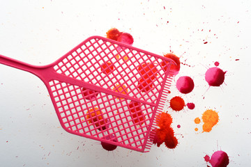 Fly swatter with splashes of fake blood from swatted flies and insects