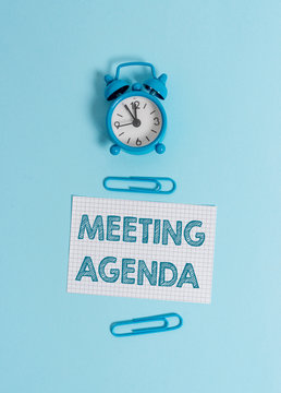 Handwriting text writing Meeting Agenda. Conceptual photo items that participants hope to accomplish at a meeting Alarm clock wakeup squared blank paper sheet clips colored background