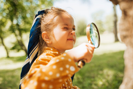 Curious kid with magnifying glass exploring the nature outdoor. Adorable little explorer girl playing in forest with magnifying glass. Child looking through magnifier on a sunny day in park