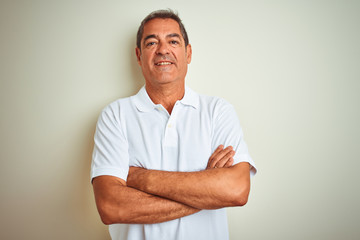 Handsome middle age man wearing polo standing over isolated white background happy face smiling with crossed arms looking at the camera. Positive person.