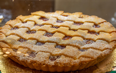 Crostata, pie with apricot jam and white sugar.