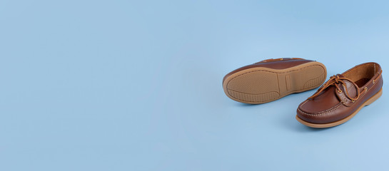 Brown mens topsiders shoes on blue background with reflection. Fashion advertising shoes. Copy space