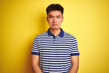 Young asian chinese man wearing striped polo standing over isolated yellow background depressed and worry for distress, crying angry and afraid. Sad expression.