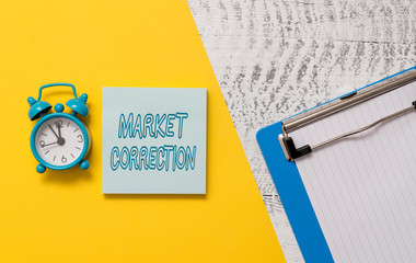 Conceptual hand writing showing Market Correction. Concept meaning When prices fall 10 percent from the 52 week high Notepad colored paper sheet alarm clock wooden background