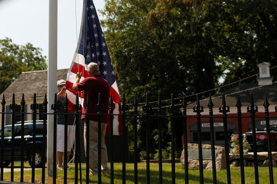 People raise a U.S. flag on a flagpole in Barnstable Village on Cape Cod, Massachusetts