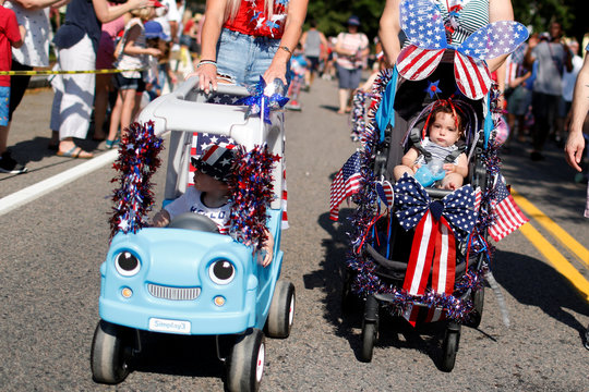 Children are pushed in decorated strollers during the annual 4th of July parade in Barnstable Village