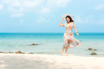 Summer Holiday. Lifestyle smiling asian woman wearing dress fashion summer trips relax on the sandy ocean beach. Happy woman enjoy and relax vacation. Lifestyle and Travel Concept.