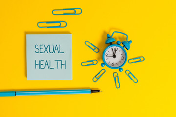 Word writing text Sexual Health. Business photo showcasing positive and respectful approach to sexual relationships Metal alarm clock wakeup clips ballpoint notepad colored background