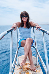 beautiful, tanned woman sitting on the bow of the yacht