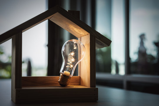 Light bulb with wood house on the table, a symbol for construction, Creative light bulb idea, power energy or business idea concept ecology, loan, mortgage, property or home.