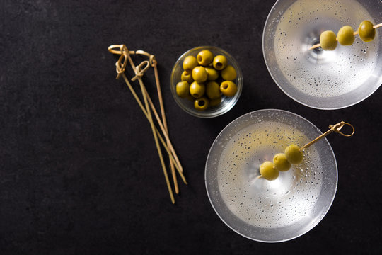 Classic Dry Martini with olives isolated on black background. Top view. Copyspace
